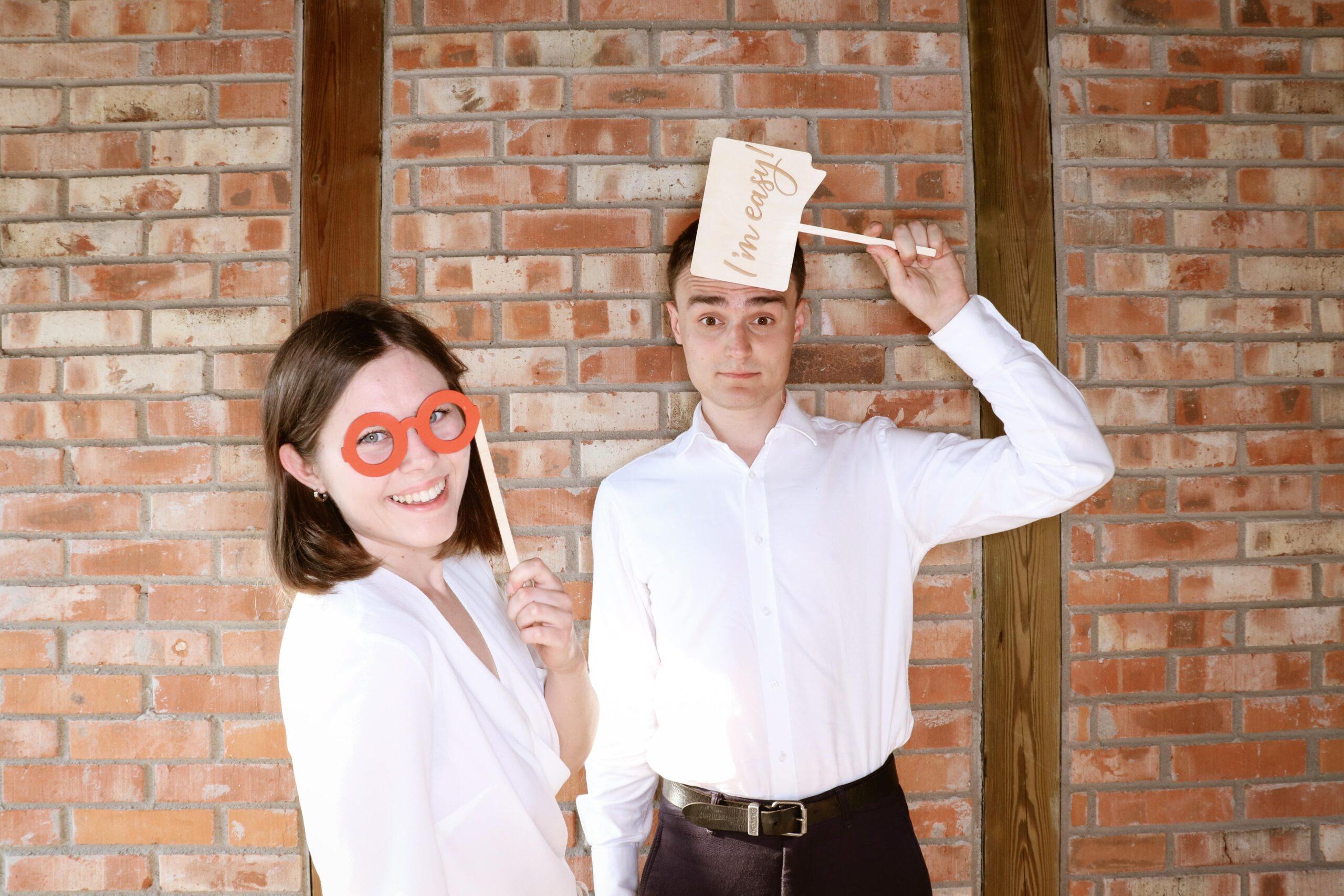 Osoba pozująca do zdjęcia przed fotobudką ubrana z gadżetami